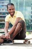 Smiling youth on skateboard — Stock Photo