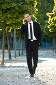 Businessman walking in the park with cell phone — Stock Photo