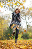 Woman Kicking Yellow Leaves in Autumn — Stock Photo