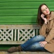 Woman Listening on Mobile Phone Outdoors - Stock Photo