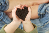 Child Hands Holding Soil in Heart Shape — Stock Photo