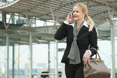 Portrait of a traveling business woman talking on mobile phone outdoors — Stock Photo