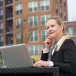 Modern business woman sitting with laptop outdoors — Stock Photo