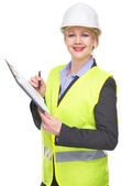 Portrait of a smiling woman in safety vest and hardhat writing on clipboard — Stock Photo