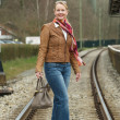 Portrait of a happy woman crossing train tracks with bag — Stock Photo #24437925