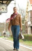 портрет красивые зрелые женщины, стоя на платформе станции поезда — Стоковое фото