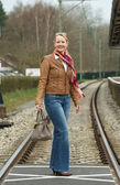Portrait of a happy woman crossing train tracks with bag — Stock Photo