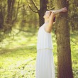 Beautiful young bride in white wedding dress leaning against tree outdoors — Stock Photo
