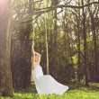 Portrait of a beautiful young bride sitting alone on swing outdoors — Stock Photo