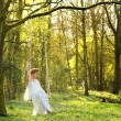 Elegant bride in white wedding dress sitting alone on swing outdoors -  