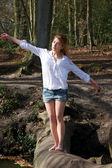 Beautiful young woman balancing on a log across a stream — Stock Photo