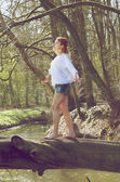 Retrato de una mujer joven equilibrando en tronco de árbol caído en corriente — Foto de Stock