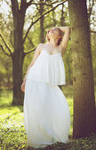Beautiful young bride in white wedding dress posing against tree — Stock Photo