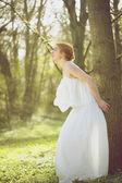 Beautiful young bride in white wedding dress standing outdoors — Stock Photo