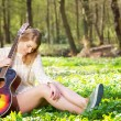 Portrait of a beautiful blond woman relaxing with guitar under tree — Stock Photo #24538501