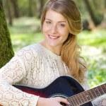 Retrato de una joven atractiva, sonriendo con la guitarra al aire libre — Foto de Stock