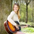 Portrait of a young woman smiling with guitar outdoors — Stock Photo