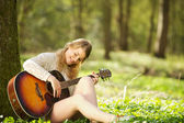 Portrait of a beautiful young woman playing guitar outdoors — Stock Photo