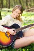 Closeup portrait of a beautiful young woman playing guitar — Stock Photo