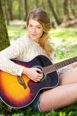 Portrait of an attractive young woman playing guitar outdoors — Stock Photo