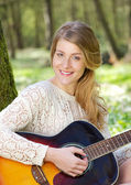 Portrait of an attractive young woman smiling with guitar outdoors — Stock Photo