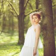 Beautiful woman in white dress posing in forest - Stock Photo