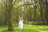 Portrait of a happy bride in white wedding dress sitting on a swin in the wood — Stock Photo