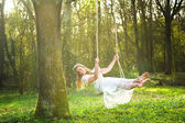 Beautiful bride in white wedding dress smiling and swinging in the forest — Stock Photo