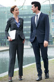Businessman and business woman walking together outdoors — Stock Photo