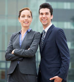 Relaxed businessman and business woman smiling — Stock Photo