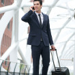 Businessman traveling and talking on phone at station — Stock Photo
