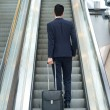 Business man going up escalator with bag — Stock Photo