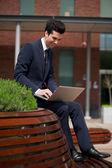 Młody biznesmen działa na laptopie poza biurem — Zdjęcie stockowe