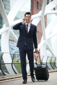 Confident businessman traveling with phone and bag — Stock Photo