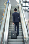 Business man going up escalator with bag — Zdjęcie stockowe