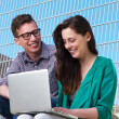 Two students working together on laptop outdoors — Stock Photo