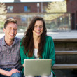 Stock Photo: Happy students sitting outdoors with laptop