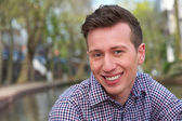 Horizontální portrét pohledného mladíka s úsměvem venku — Stock fotografie
