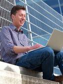 Ung man leende på laptop utomhus — Stockfoto