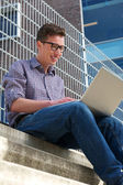 College student working on laptop outdoors — Stock Photo