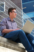 University student working on laptop outdoors — Stock Photo