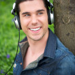 Handsome young man listening to music outdoors — Stock Photo