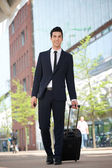 Handsome businessman walking outdoors with bag — Stock Photo