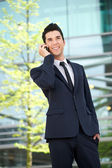 Happy businessman talking on mobile phone outdoors — Stock Photo