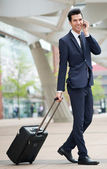 Traveling businessman talking on phone outdoors — Stock Photo