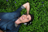 Young man relaxing with headphones outdoors - from above — Stock Photo