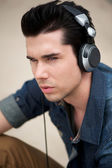 Attractive man listening to music on headphones outdoors — Stock Photo