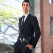 Young businessman walking in the city - Stock Photo