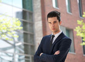 Businessman standing outdoors with arms crossed — Stock Photo