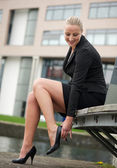 Portrait of a young business woman adjust her shoes — Stock Photo